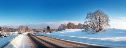 Asphalt road in snowy winter on beautiful sunny day Stock Images