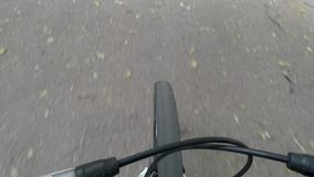 Asphalt road and spinning bicycle front wheel, top down view. stock footage