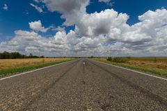 Asphalt road in the steppe and clouds in the blue sky. Horizontal royalty free stock photography