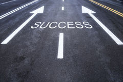 Asphalt road with success word. And white arrow marking on road, business challenge concept Stock Image