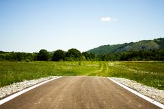Asphalt road suddenly ending in the middle of nowhere. Paved road ending abruptly in the middle of a green plain with some trails ahead Royalty Free Stock Photos
