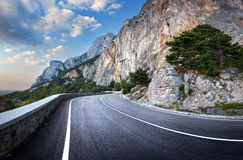 Asphalt road in summer forest at sunset. Crimean mountains Royalty Free Stock Photos