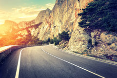 Asphalt road in summer forest at sunset. Crimean mountains Royalty Free Stock Photography