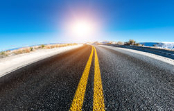 Asphalt road and the sun in the sky Stock Image
