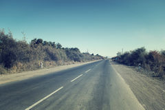 Asphalt road on a sunny summer day. An asphalt road without cars on a summer day Royalty Free Stock Image