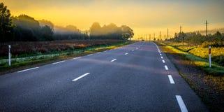 Asphalt road at sunrise royalty free stock photo
