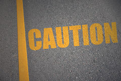 Asphalt road with text caution near yellow line Stock Photo