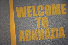 Asphalt road with text welcome to abkhazia near yellow line. Concept Royalty Free Stock Photo