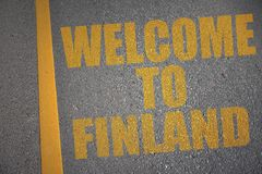 Asphalt road with text welcome to finland near yellow line. Concept Stock Photo