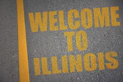 Asphalt road with text welcome to illinois near yellow line. Concept Royalty Free Stock Photography