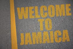 asphalt road with text welcome to jamaica near yellow line. Royalty Free Stock Image