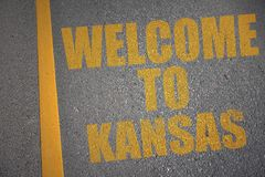 Asphalt road with text welcome to kansas near yellow line. Stock Photo