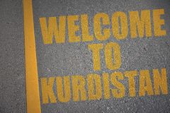 Asphalt road with text welcome to kurdistan near yellow line. Concept Royalty Free Stock Images