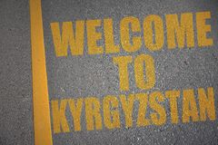 asphalt road with text welcome to kyrgyzstan near yellow line. Royalty Free Stock Photos