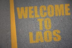 asphalt road with text welcome to laos near yellow line. stock photography