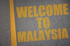 asphalt road with text welcome to malaysia near yellow line. Royalty Free Stock Images