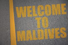 asphalt road with text welcome to maldives near yellow line. Royalty Free Stock Images