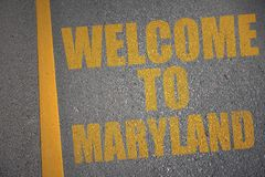 asphalt road with text welcome to maryland near yellow line. stock photo