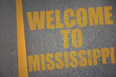 asphalt road with text welcome to mississippi near yellow line. stock images