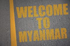 asphalt road with text welcome to myanmar near yellow line. Stock Photo