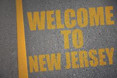 asphalt road with text welcome to new jersey near yellow line. Royalty Free Stock Photo