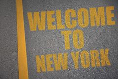 Asphalt road with text welcome to new york near yellow line. Concept Royalty Free Stock Images