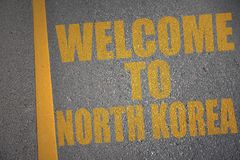 asphalt road with text welcome to north korea near yellow line. Royalty Free Stock Photography