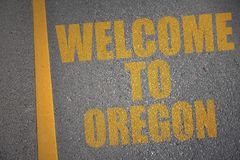Asphalt road with text welcome to oregon near yellow line. Royalty Free Stock Photos