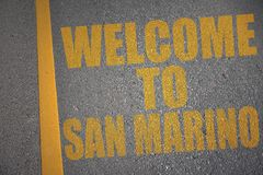 Asphalt road with text welcome to san marino near yellow line. Concept Stock Photo