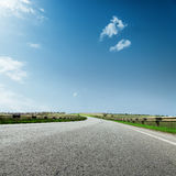 Asphalt road to horizon and blue sky with clouds Royalty Free Stock Photos