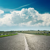 Asphalt road to horizon and clouds Royalty Free Stock Image