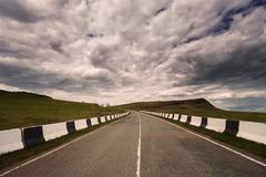 Asphalt road to horizon in cloudy sky Stock Image