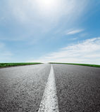 Asphalt road to horizon under sky with clouds Royalty Free Stock Images