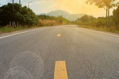Asphalt road to the mountains ahead. Stock Photo