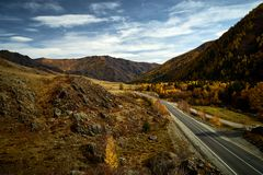 Asphalt road to the mountains of Altai passing through the autumn landscape royalty free stock photography