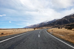 Asphalt road to the National Park Mount Cook. Stock Images