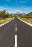 Asphalt road towards mountains Stock Photos
