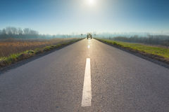 Asphalt road towards sun and upcoming tractor Royalty Free Stock Photo