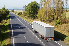 Asphalt road between the trees in the countryside. Two white trucks on the road. Stock Image