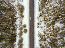 Forest road in winter view from above. Asphalt road and trees in the forest in winter view from above royalty free stock image