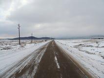 Asphalt road trough snowy field. In a dark winter day Stock Image