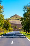 Asphalt road and typical conical volcanic hill of Central Bohemian Highlands on sunny summer day, Czech Republic.  stock photo