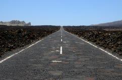 Asphalt road under blue sky. Dark asphalt surface Royalty Free Stock Photography