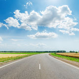 Asphalt road under clouds Royalty Free Stock Photos