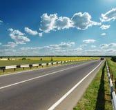 Asphalt road under cloudy sky Stock Photos