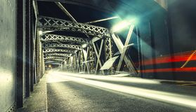 Asphalt road under the steel construction of a bridge in the city. Night urban scene with car light trails in the tunnel Stock Photo