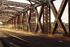 Asphalt road under the steel construction of a city bridge on a sunny day. Urban scene in the bridge tunnel. Long Royalty Free Stock Photography