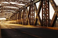 Asphalt road under the steel construction of a city bridge on a sunny day. Urban scene in the bridge tunnel. Long Royalty Free Stock Image