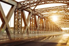 Asphalt road under the steel construction of a city bridge on a sunny day. Urban scene in the bridge tunnel. Long Royalty Free Stock Photos