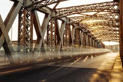 Asphalt road under the steel construction of a city bridge on a sunny day. Urban scene in the bridge tunnel. Long Stock Images